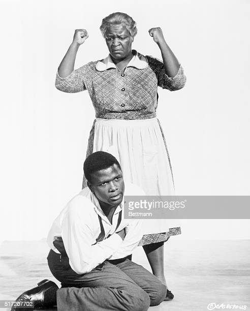 Actor Sidney Poitier is shown on his knees with the actress who portrays his mother standing above him fists raised in frustration in this scene from...