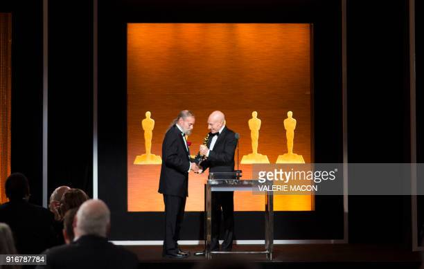 Actor Sir Patrick Stewart gives the Oscar to Visual effects technologist Jonathan Erland recipient of the Gordon E Sawyer Award during the Academy of...