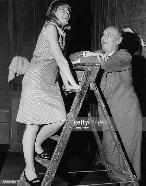 Actor Sir Ralph Richardson looking up at actress Barbara Ferris who is climbing a step ladder during rehearsals for the play 'Carving a Statue'...