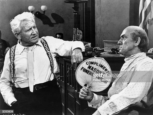 Actor Spencer Tracy crossexamines Fredric March in a courtroom as he fans himself in a still from the film Inherit the Wind