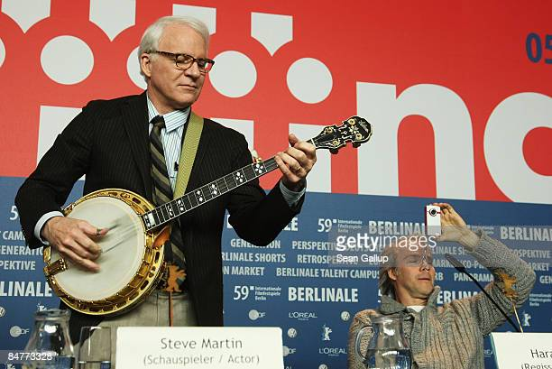 Actor Steve Martin plays the Banjo while director Harald Zwart takes pictures of the audience at the press conference for 'Pink Panther 2' as part of...