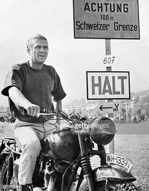 Actor Steve McQueen sitting on a motorcycle next to a road sign.