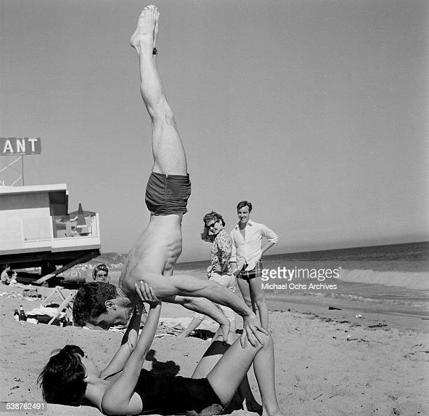 Actor Steve Rowland balances on actress Natalie Wood during the Thalians Beach Ball in MalibuCalifornia
