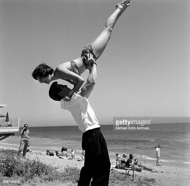 Actor Steve Rowland lifts actress Natalie Wood during the Thalians Beach Ball in MalibuCalifornia