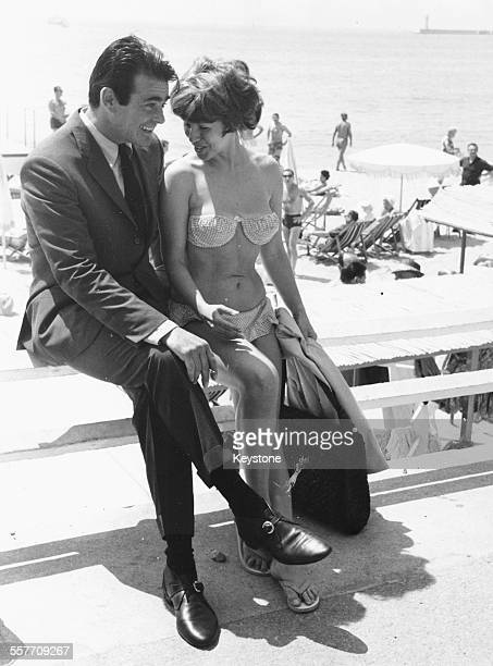 Actor Stuart Whitman sitting beside French actress Cynthia Granier on the beach taking a break from promoting his movie 'The Mark' at the Cannes Film...