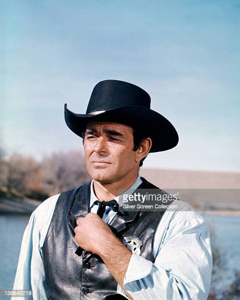 US actor Stuart Whitman wearing a black Western hat and black leather waistcoat with a sheriff's badge in a scene from the American western...