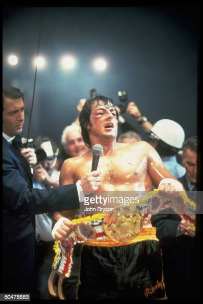 Actor Sylvester Stallone holding championship belt surrounded by reporters after winning fight in scene fr motion picture Rocky V
