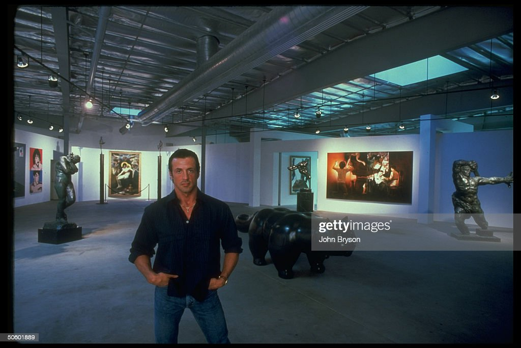 Actor Sylvester Stallone in lobby of office in front of his art collection, incl. Eve by Rodin, Two Sides of Sly by Warhol, Bouguereau's Pie.