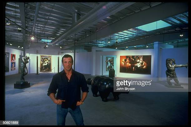 Actor Sylvester Stallone in lobby of office in front of his art collection incl Eve by Rodin Two Sides of Sly by Warhol Bouguereau's Pie