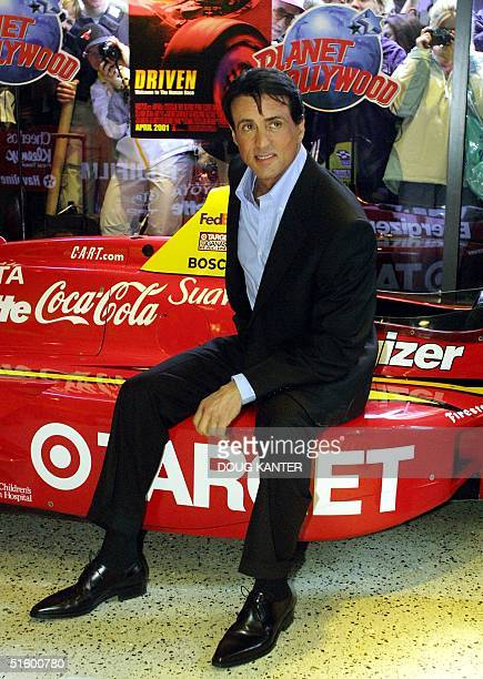 Actor Sylvester Stallone poses at Planet Hollywood in New York with a replica of a car from his new movie 'Driven' 26 April 2001 Stallone stars in...