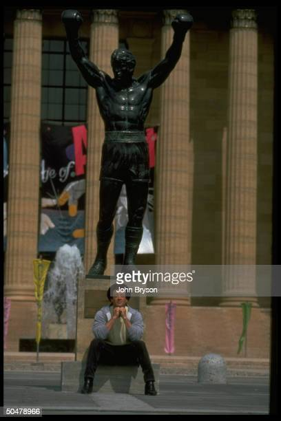 Actor Sylvester Stallone sitting under statue of Rocky Balboa character he made famous in Rocky films