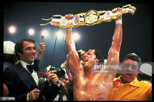 Actor Sylvester Stallone victoriously holding championship belt over head while reporters watch in scene fr motion picture Rocky V