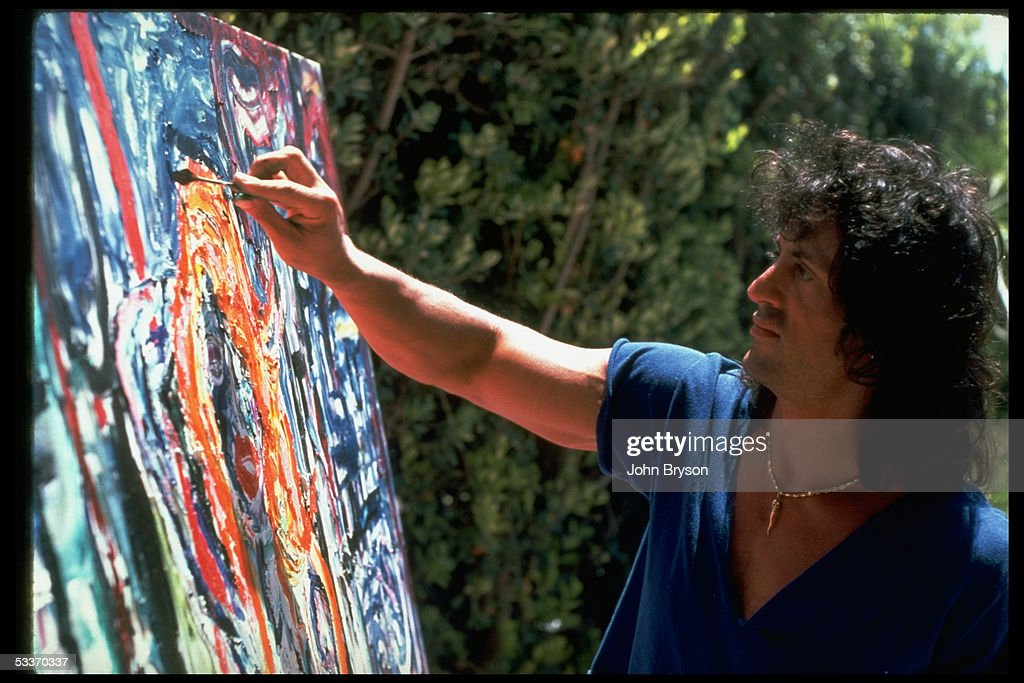 Actor Sylvester Stallone working on painting using palette knife outside at home.