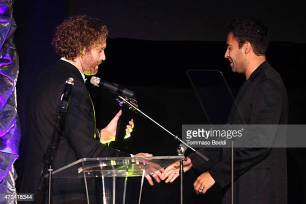 Actor T J Miller honors Editor David Schumann with the Golden Trailer Award for Best Summer 2015 Blockbuster Trailer on behalf of the crew on stage...