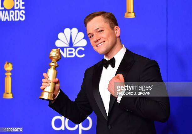 Actor Taron Egerton poses in the press room with the award for Best Performance by an Actor in a Motion Picture - Musical or Comedy during the 77th...