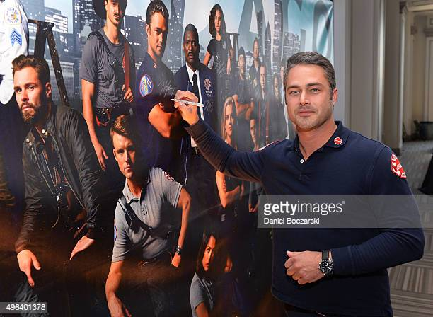 Actor Taylor Kinney signs a poster as he attends a press junket for NBC's 'Chicago Fire' 'Chicago PD' and 'Chicago Med' at Cinespace Chicago Film...
