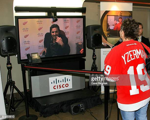 Actor Thorsten Kaye of ABC daytime drama All My Children interacts with a Detroit Red Wings fan using Cisco TelePresence before game one of the...