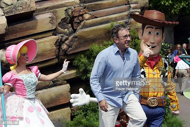 Actor Tim Allen is escorted by Bo Peep and Woody as he arrives at the official opening of the new Tomorrowland attraction Buzz Lightyear Astro...