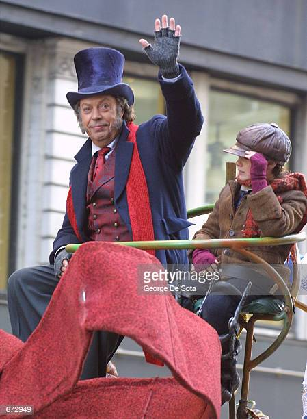 Actor Tim Curry dressed as Scrooge from A Christmas Carol waves to the crowds while riding on a float in the 75th annual Macy's Thanksgiving Day...