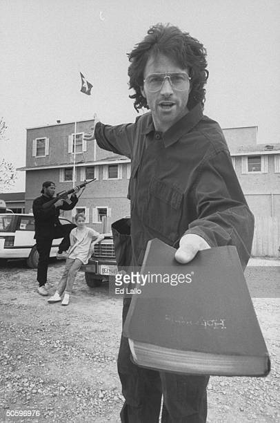 Actor Tim Daly holds up bible and gestures as he stands outside on the set of the cult compound as an armed male actor stands guard with a female...