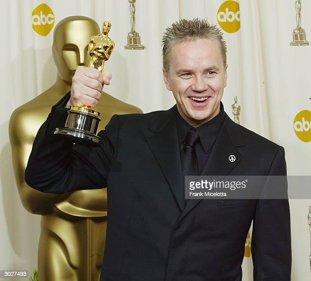 Actor Tim Robbins poses with his Oscar for Best Supporting Actor during the 76th Annual Academy Awards at the Kodak Theater on February 29, 2004 in...
