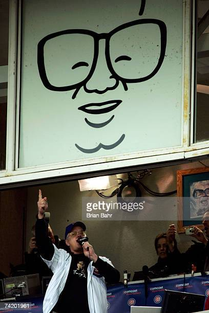 Actor Tim Robbins sings Take Me Out to the Ball Game under a caricature of Harry Caray during the seventh inning stretch in a game between the...