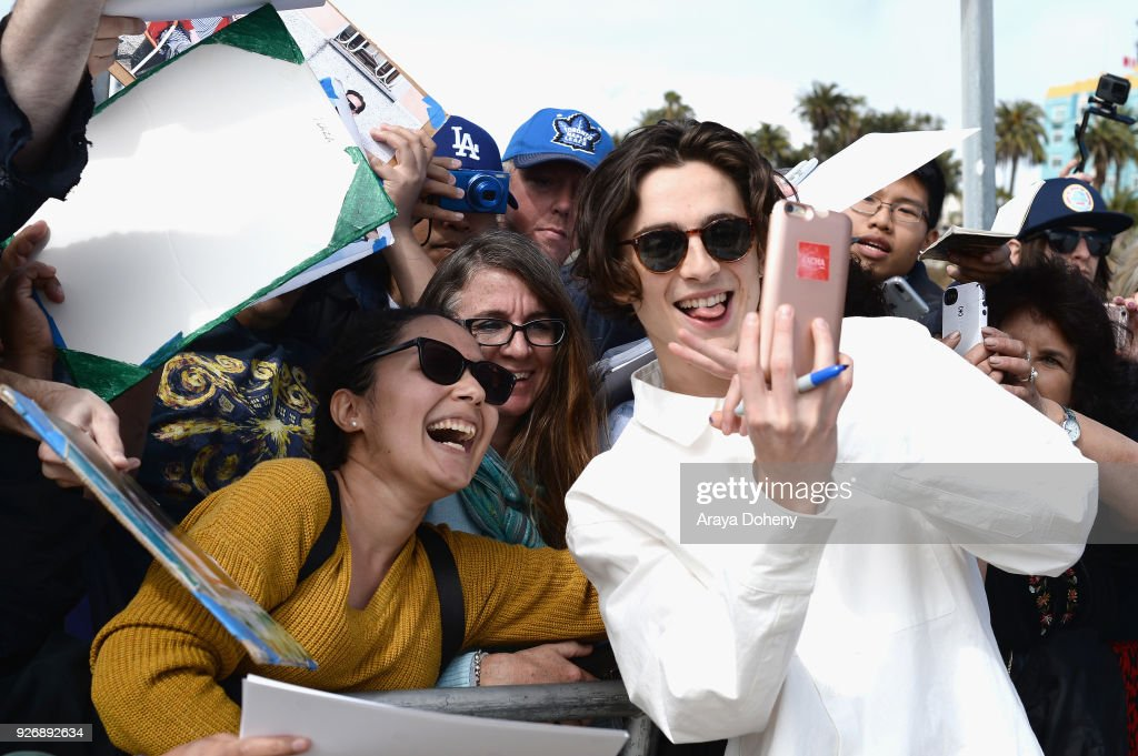Actor Timothee Chalamet (R) poses for a selfie with fans during the 2018 Film Independent Spirit Awards on March 3, 2018 in Santa Monica, California.