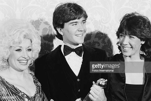 Actor Timothy Hutton holding his award for the film 'Ordinary People' with actress Lily Tomlin and singer Dolly Parton at the Golden Globe Awards at...