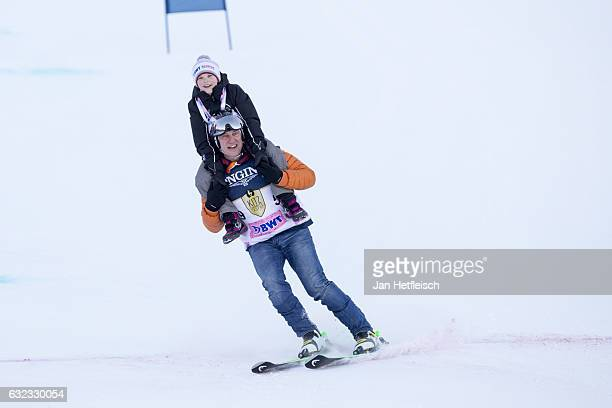 Actor Tobias Moretti speeds down the slope with a kid on his shoulders during the KitzCharityTrophy on January 21 2017 in Kitzbuehel Austria