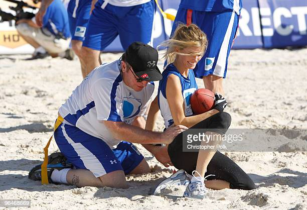 Actor Tom Arnold tackles model Marisa Miller attend the Fourth Annual DIRECTV Celebrity Beach Bowl at DIRECTV Celebrity Beach Bowl Stadium South...