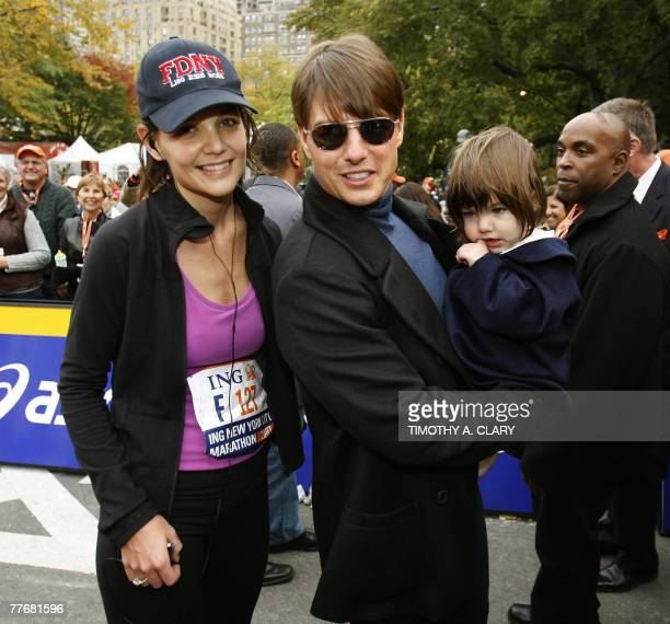 US actor Tom Cruise and his daughter Suri wait at the finish line to greet his wife Katie Holmes after she finished running the New York City...