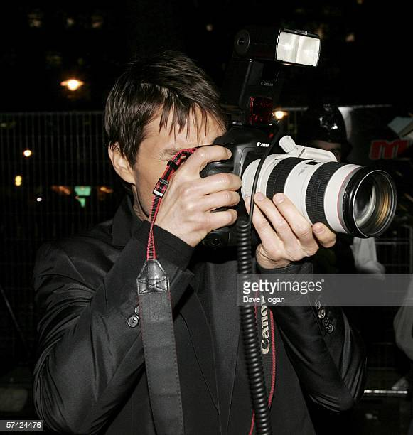 Actor Tom Cruise borrows a camera from a photographer to photograph the press at the UK Premiere of 'Mission Impossible 3' the third film in the...
