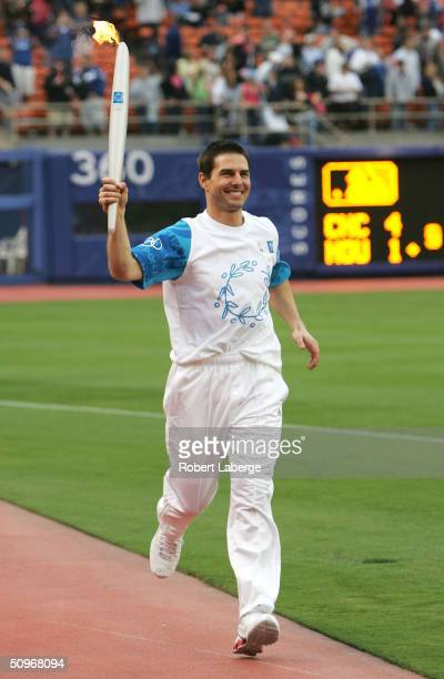 Actor Tom Cruise enters Dodgers Stadium with the Olympic Torch during the torch relay on June 16 2004 at Dodger Stadium in Los Angeles California