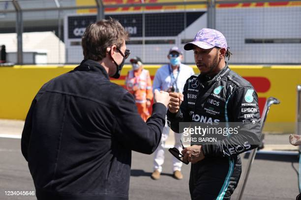 Actor Tom Cruise fist bumps Mercedes' British driver Lewis Hamilton after the Formula One British Grand Prix motor race at Silverstone motor racing...