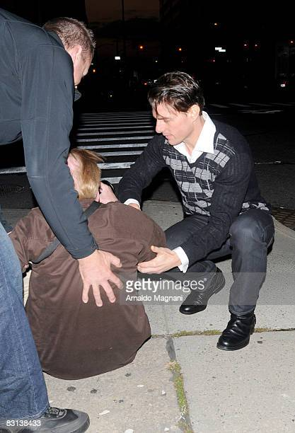 Actor Tom Cruise helps a photographer up after falling on October 5 2008 in New York City