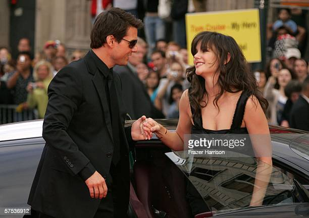 Actor Tom Cruise helps his fiancee Katie Holmes out of the car as they arrive at the Paramount Pictures fan screening of 'Mission Impossible III'...
