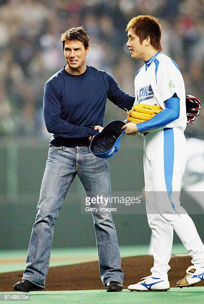 Actor Tom Cruise is seen with an unidentified player from the Pacific League champion Seibu Lions on the mound after throwing the ceremonial first...