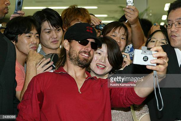Actor Tom Cruise poses for photos with Japanese fans in the arrival lobby at Haneda Airport August 28 2003 in Tokyo Japan Cruise is currently on a...