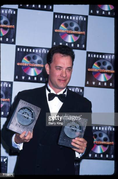 Actor Tom Hanks holds two award plaques at the Blockbuster Entertainment Awards March 6 1996 in Los Angeles CA Hanks was honored as Favorite Actor in...