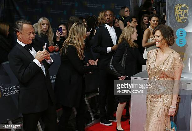 Actor Tom Hanks prepares to take a picture of his wife Rita Wilson as they arrive on the red carpet for the BAFTA British Academy Film Awards at the...