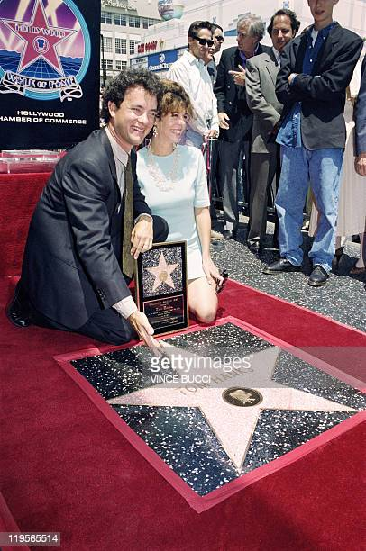 Actor Tom Hanks shows off his star on the Hollywood Walk of Fame 30 June 1992 during a ceremony honoring movie and television stars Hanks' current...
