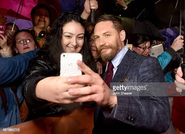Actor Tom Hardy takes a selfie with a fan while attending the 'Legend' gala screening during the 2015 Toronto International Film Festival at Roy...
