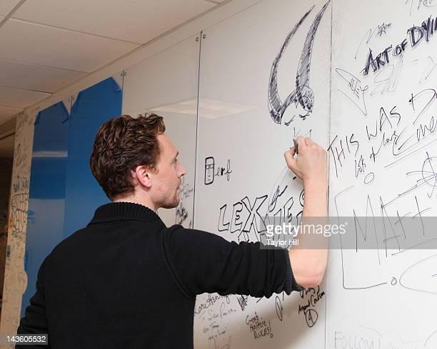 Actor Tom Hiddleston draws Loki on the wall at SiriusXM Studio on April 30, 2012 in New York City.