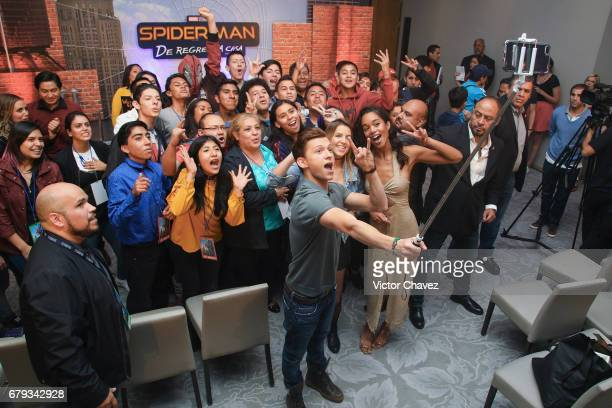 Actor Tom Holland and Laura Harrier take a selfie with fans during Los 40 Principales fan event to promote the new film SpiderMan Homecoming at St...
