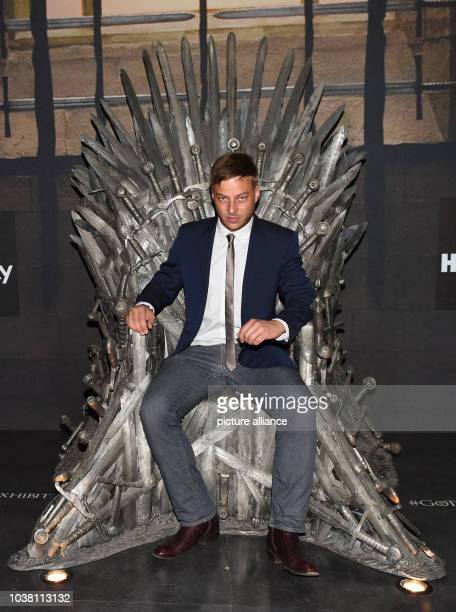Actor Tom Wlaschiha poses on the 'Iron throne' a prop of the US television show 'Game of Thrones' on display during the preopening event of the...