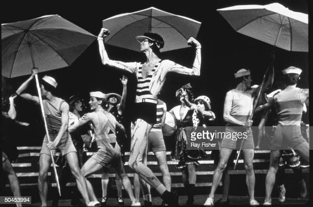 Actor Tommy Tune flexing his muscles with cast members in a scene from the stage musical Mack and Mabel