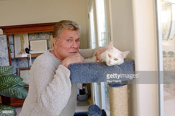 Actor Tony Curtis poses for a portrait with his cat at his home March 15 2002 Las Vegas Nevada