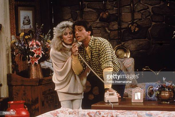 Actor Tony Danza eavesdrops as Judith Light speaks on the telephone in a still from the TV series 'Who's The Boss' circa 1986