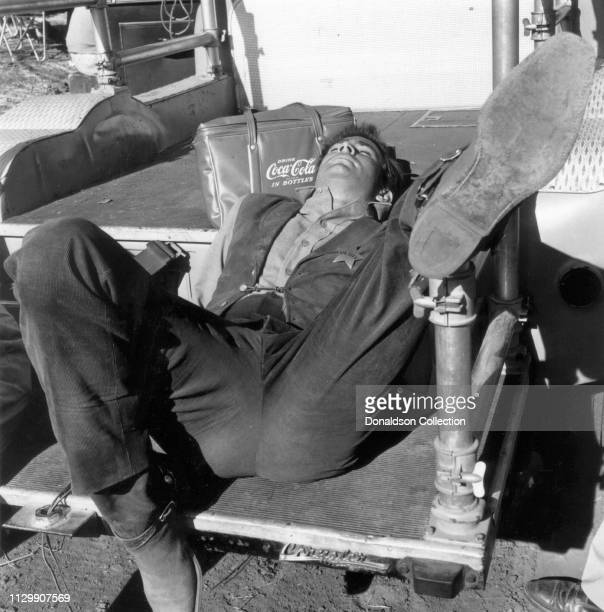 Actor Tony Perkins leans on a CocaCola bag on the set of the movie 'The Tin Star' in 1957