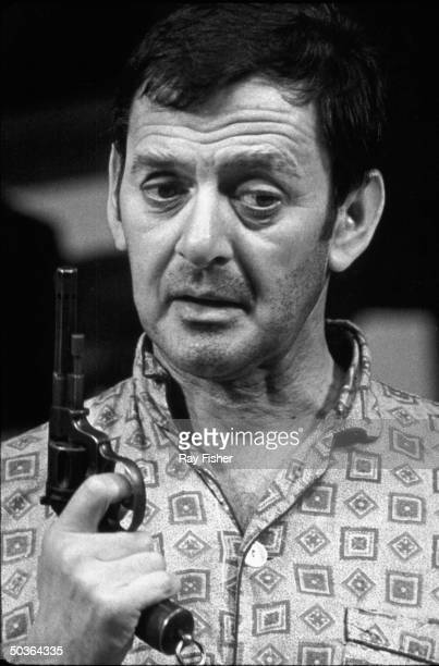 Actor Tony Randall holding a gun in a scene from the stage play The Button